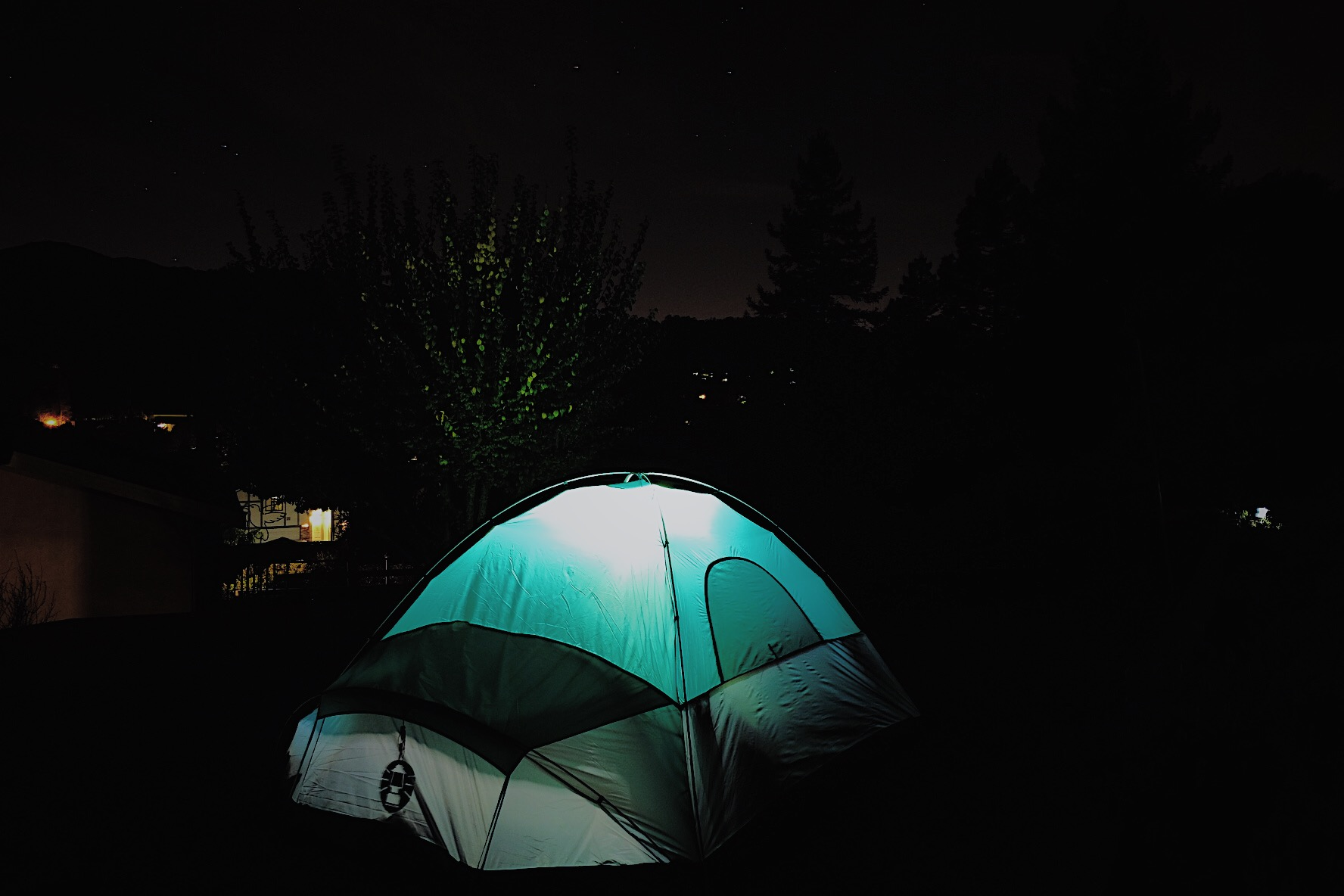 A night time photo of a tent illuminated from inside.