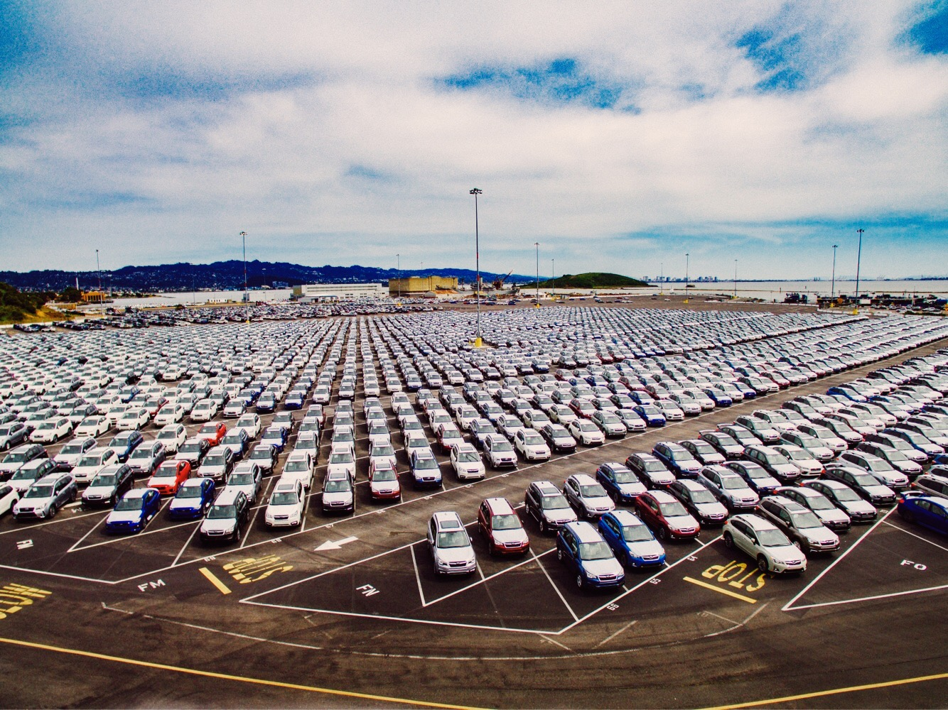 An overhead picture of a storage lot for new cars.