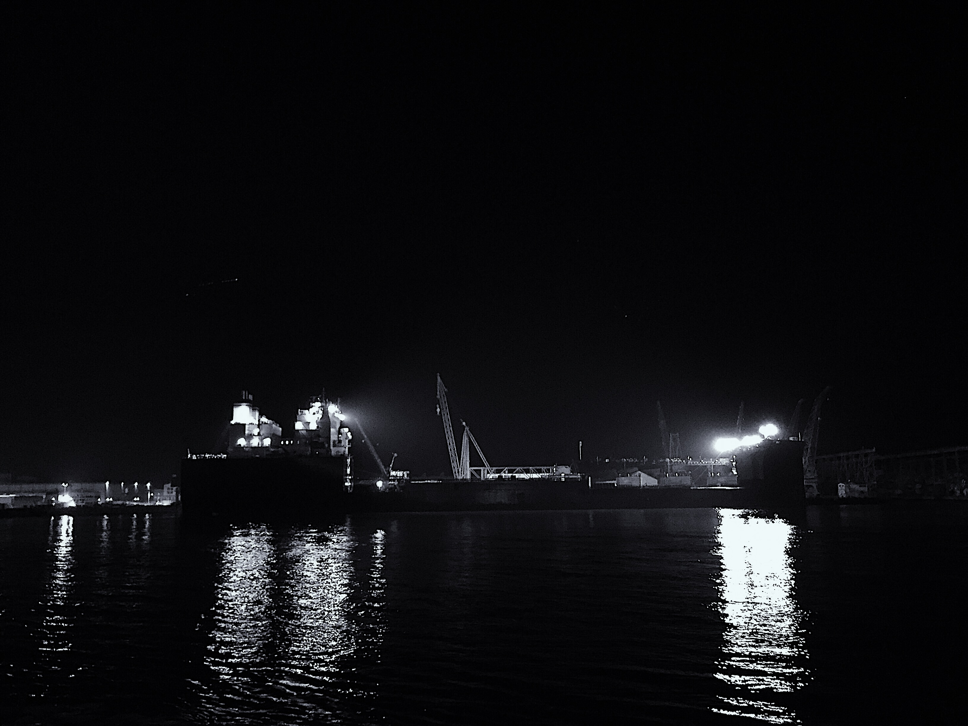 A night time photo of a cargo ship being serviced in a shipyard.
